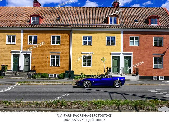 Stockholm, Sweden A fancy sports car driving by brightly colored houses along Alviksvagen in Appelviken