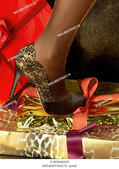 Human leg in high heels steps on wrapped christmas presents