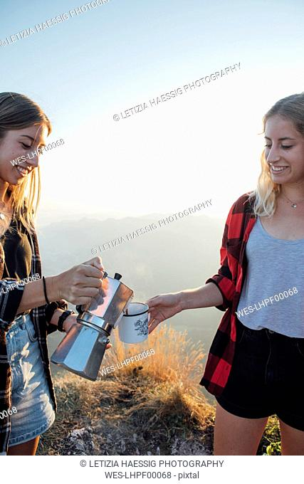 Young woman on a hiking trip at sunrise pouring coffee into a cup for a friend