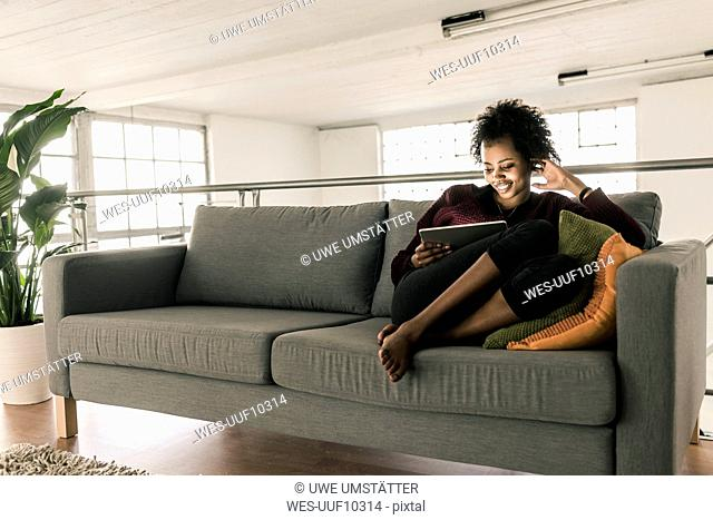 Smiling young woman sitting on couch using tablet