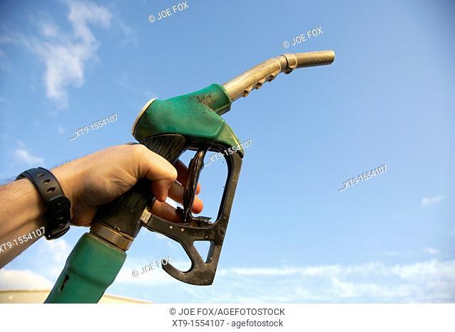mans hand holding unleaded petrol pump nozzle