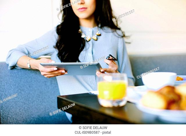 Cropped shot of young woman with digital tablet having breakfast at boutique hotel in Italy