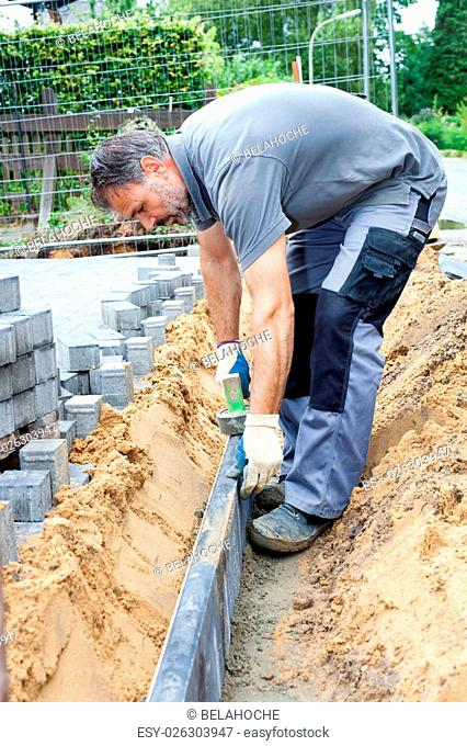 Paver separate a private property from public street by putting narrow stone slabs vertical into the ground