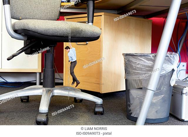 Businessman climbing down large paper clips on oversized office chair