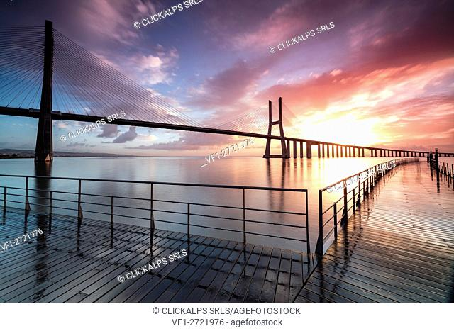 Perspective and architecture of Vasco Da Gama bridge enhanced by the colors of dawn Lisbon Portugal Europe