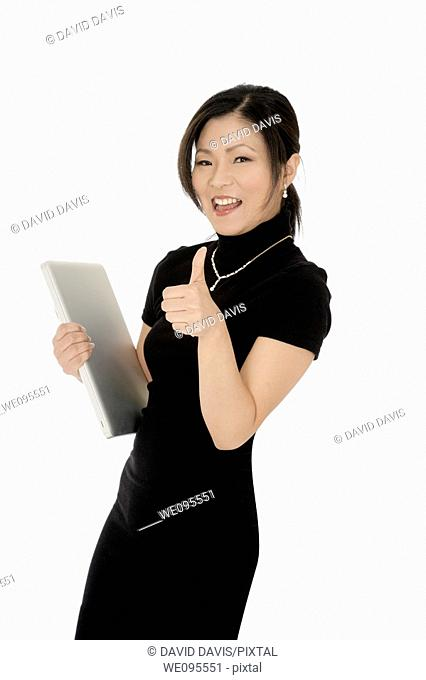 Beautiful Asian businesswoman giving the thumbs up or the ok sign