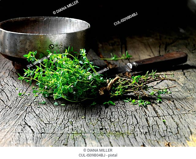 Thyme leaves tied together with string, vintage metal bowl and knife on rustic wooden surface
