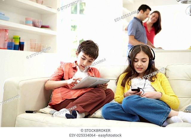 Children Playing With Digital Devices As Parents Make Meal