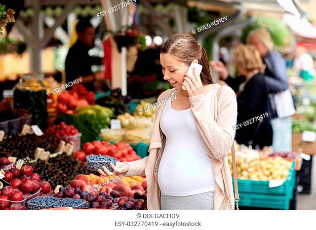 sale, shopping, food, pregnancy and people concept - happy pregnant woman choosing berries and calling on smartphone at street market