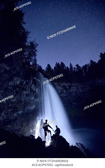 A couple holding hands in the night at the base of Canim Falls, Wells Gray Provincial Park, British Columbia, Canada