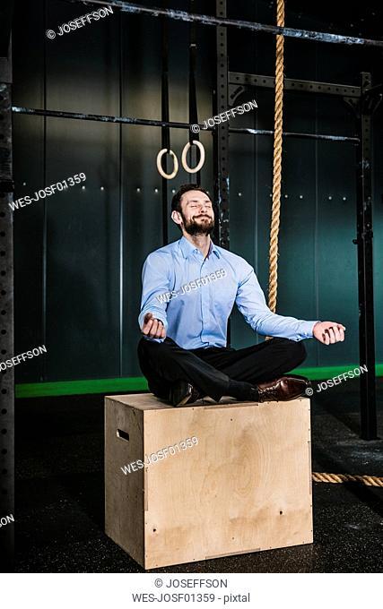 Businessman in gym siting on box, meditating