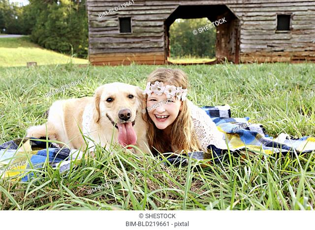 Caucasian girl laying on blanket with dog