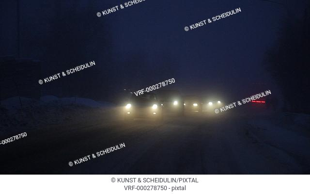 Driving on a road on a winter evening in northern Sweden. Five oncoming pairs oh headlights glide eerily through the night