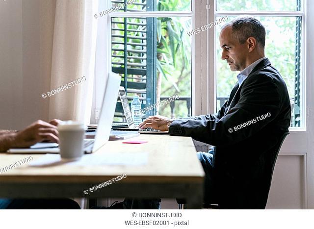 Businessman sitting at desk working on laptop