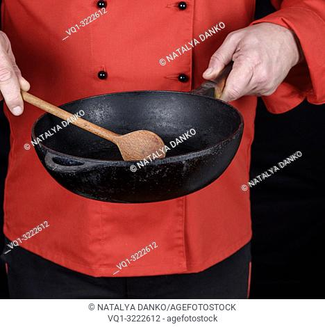 cook in red uniform holding an empty black frying pan, black background