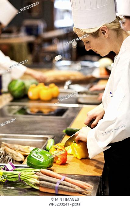 A Caucasian female chef works cutting vegetables in a commercial kitchen