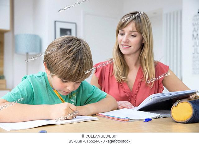 A child doing homework with his mother