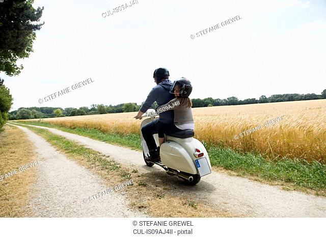 Rear view of mature man and daughter riding motor scooter along dirt track