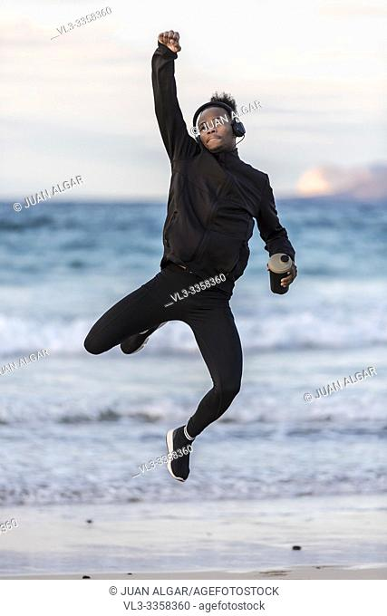 Young African American male in sportswear holding cup of hot beverage and leaping up on blurred background of amazing sea