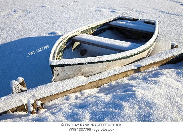 Small rowing boat covered with hoarfrost at the edge of a boating pond, Little Loch Dam, near Glasgow, Scotland