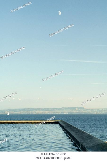 Seascape with breakwater in foreground and sailboat in distance