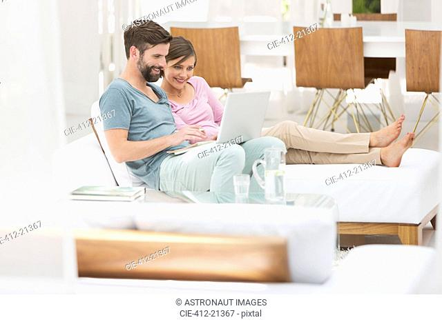 Couple using laptop together on daybed in modern living room