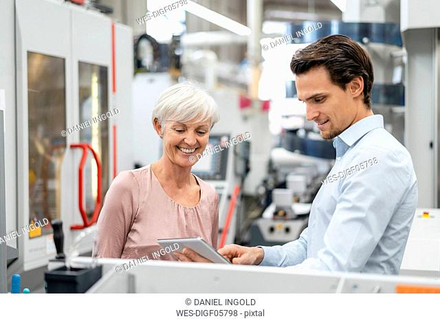 Smiling businessman and senior woman with tablet talking in a factory