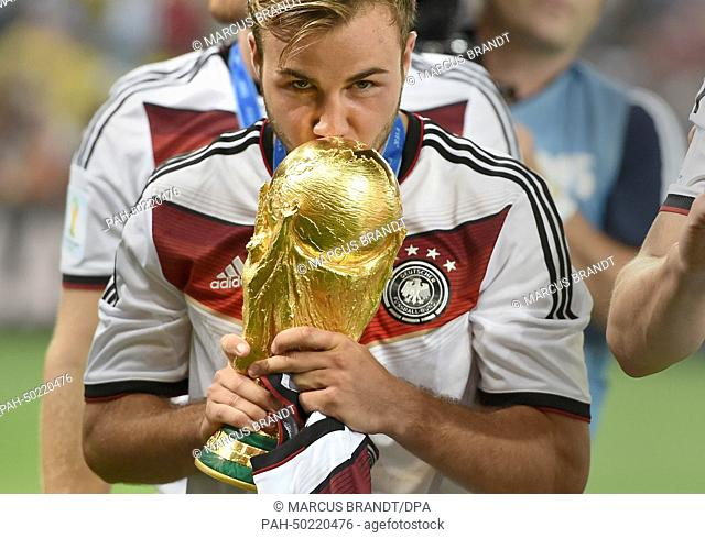 Mario Goetze of Germany kisses the World Cup trophy after winning the FIFA World Cup 2014 final soccer match between Germany and Argentina at the Estadio do...
