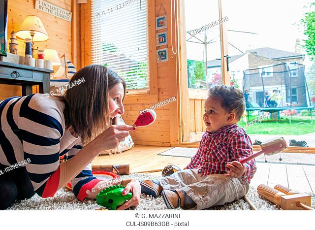 Childminder shaking maraca at baby boy