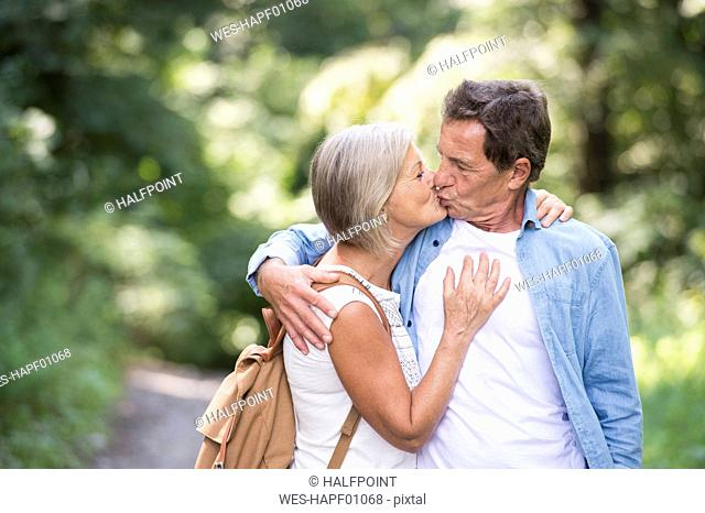 Kissing senior couple in nature