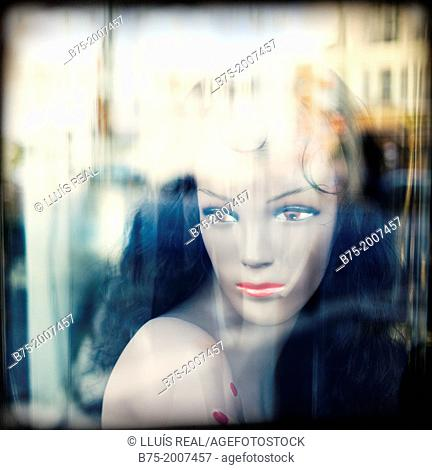 Portrait of mannequin in a shop window with reflections on the glass in Paris, France
