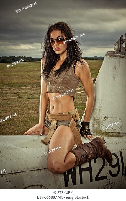 Sexy woman in skimpy shorts and boots sitting astride an old disused aircraft fuselage