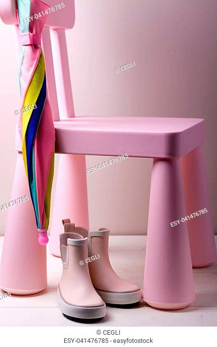 Pink little children rubber boots with colorful umbrella