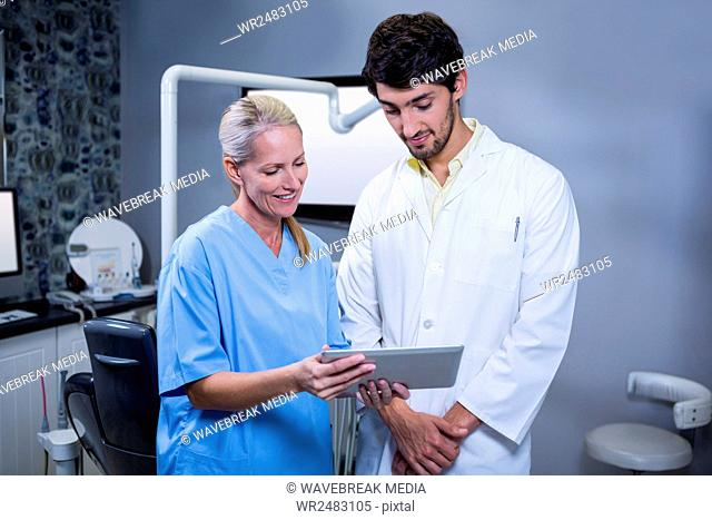 Dentist and dental assistant working together on a tablet