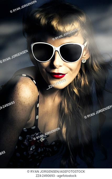 Dark night photograph of a beautiful hot woman in sunglasses at backlit nightclub wearing bright red lip cosmetics. Party fashion pin up