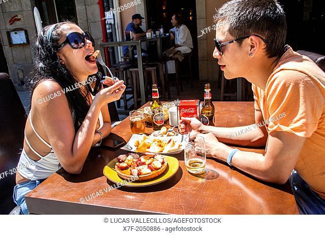 Couple in Pulperia Melide eating 'Pulpo a feira' octopus in Galician style, Plaza de España 16 or Plaza Campo de la Leña, Coruña city, Galicia, Spain