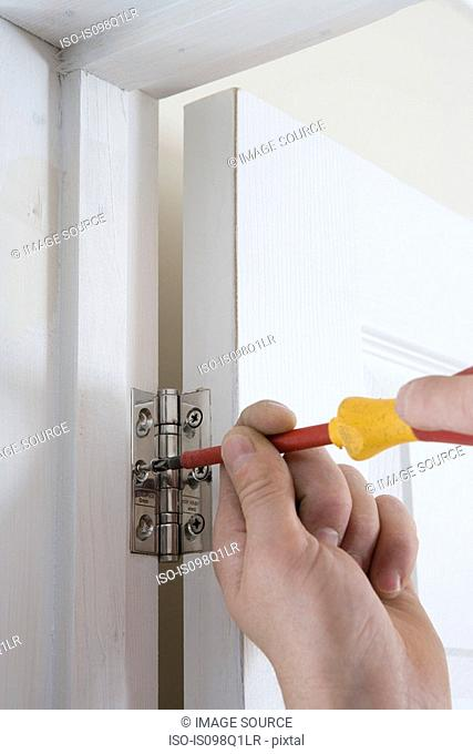 A builder fixing a door to a hinge