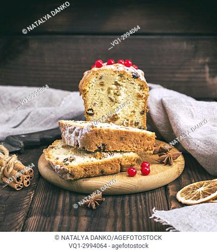large rectangular cake with raisins and dried fruits is cut into slices on a wooden board, vintage toning