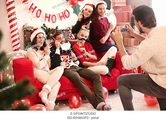 Young man photographing friends on sofa at christmas party