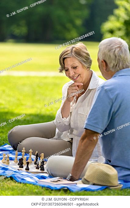 Elderly friends couple playing chess in park on sunny day