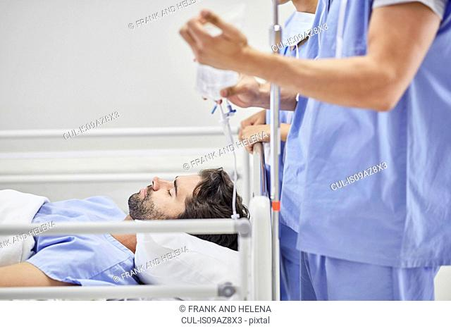 Doctor providing medical treatment to patient on hospital bed
