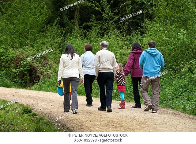 Family group walking away on forest path