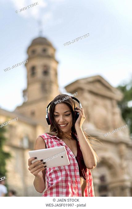 Spain, Baeza, portrait of smiling young woman using headphones and digital tablet in the city