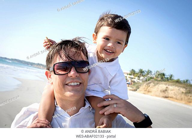 Portrait of father carrying his little son on his shoulders at the beach