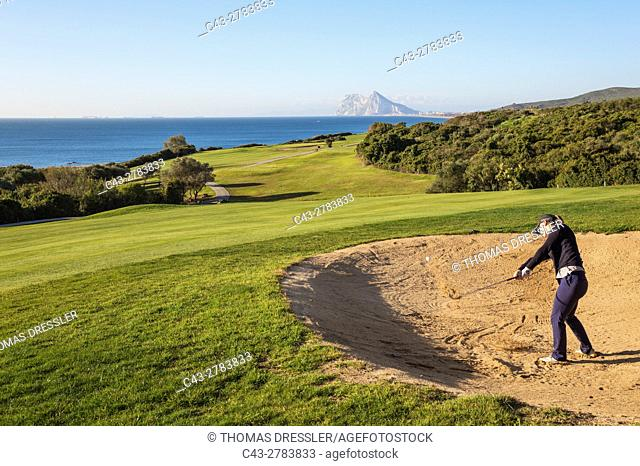 Golfer at a bunker at the La Alcaidesa Golf Resort. In the background the Mediterranean Sea with the Rock of Gibraltar (British)