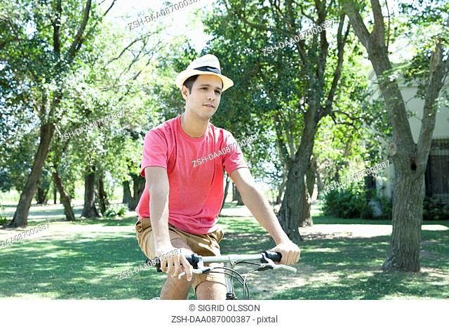 Young man riding bicycle through wooded countryside