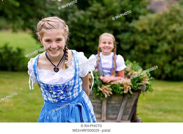 Germany, Luneburger Heide, portrait of smiling blond girl wearing dirndl pulling harvest wagon
