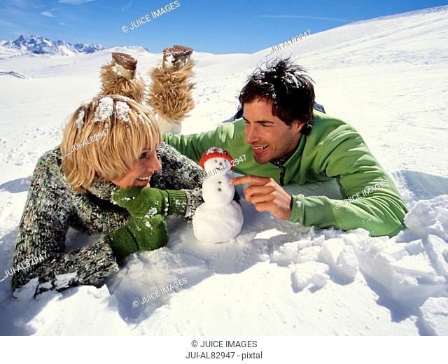 Couple laying on snow looking at tiny snowman with cap