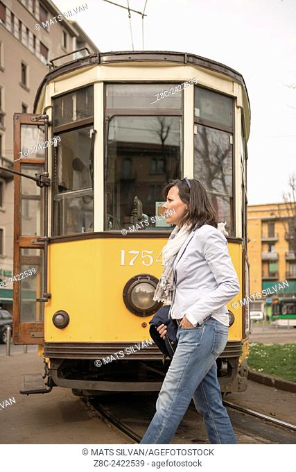 Woman crossing railroad tracks and an old Tram in background in Milan, Italy