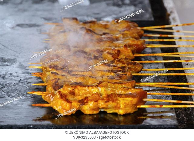 Gastronomy. Chicken skewers cooking on grille, Mijas Pueblo. Malaga province, Costa del Sol. Andalusia southern Spain. Europe